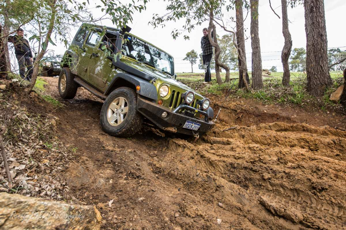 Jeep Wrangler dropping into muddy washout.