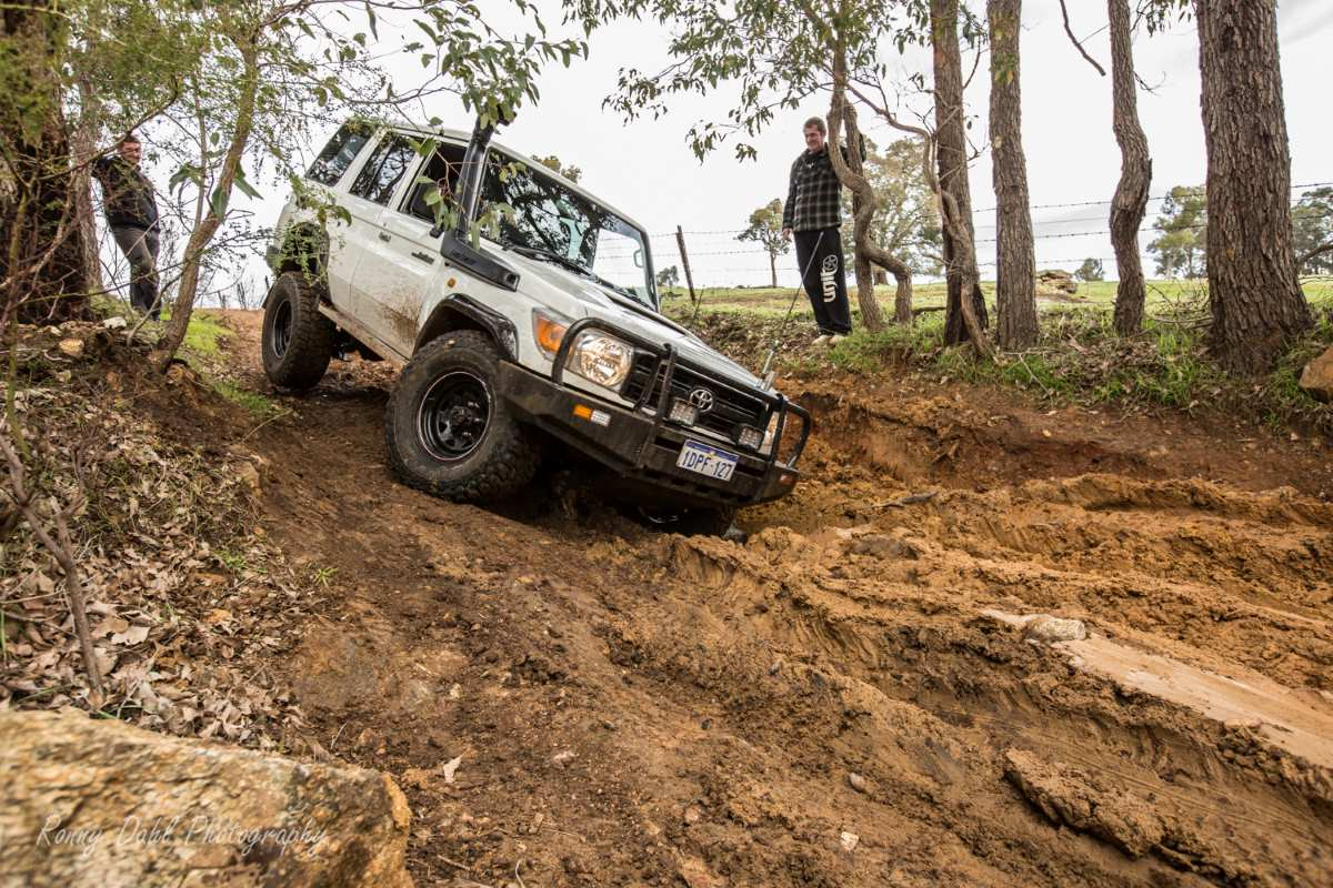 The 76 Series Land Cruiser dropping into a muddy washout.