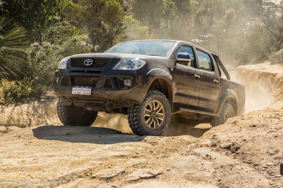 Toyota Hilux climbing a dry dusty clay track.