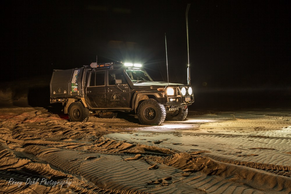 The 79 series landcruiser on the beach in the dark.