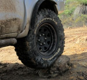 BF Goodrich Mud Terrain tire deforming around rock.