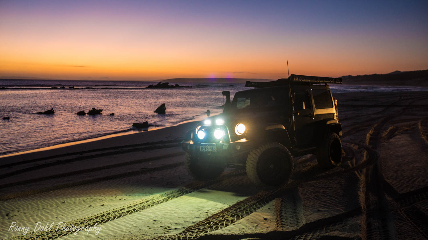 A Jeep JK Wrangler on the beach in the sunset in Western Australia.