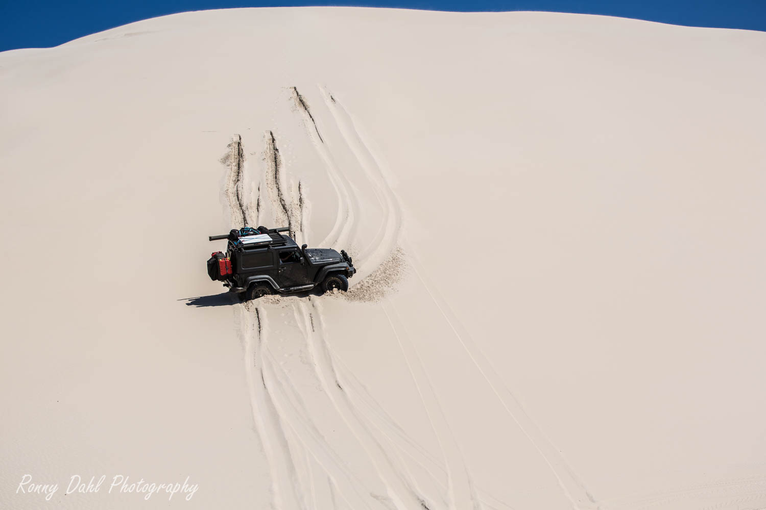 A Jeep Wrangler in trouble on a sand dune.