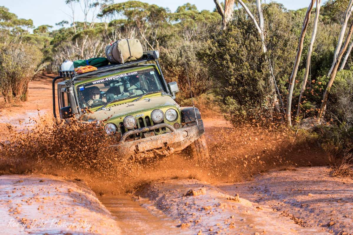 A Jeep Wrangler JKU in red mud on the Holland Track.