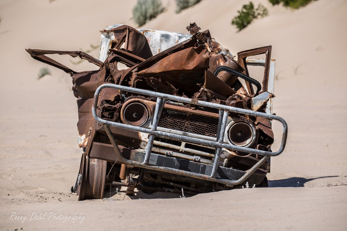 Old car in the sand dunes.