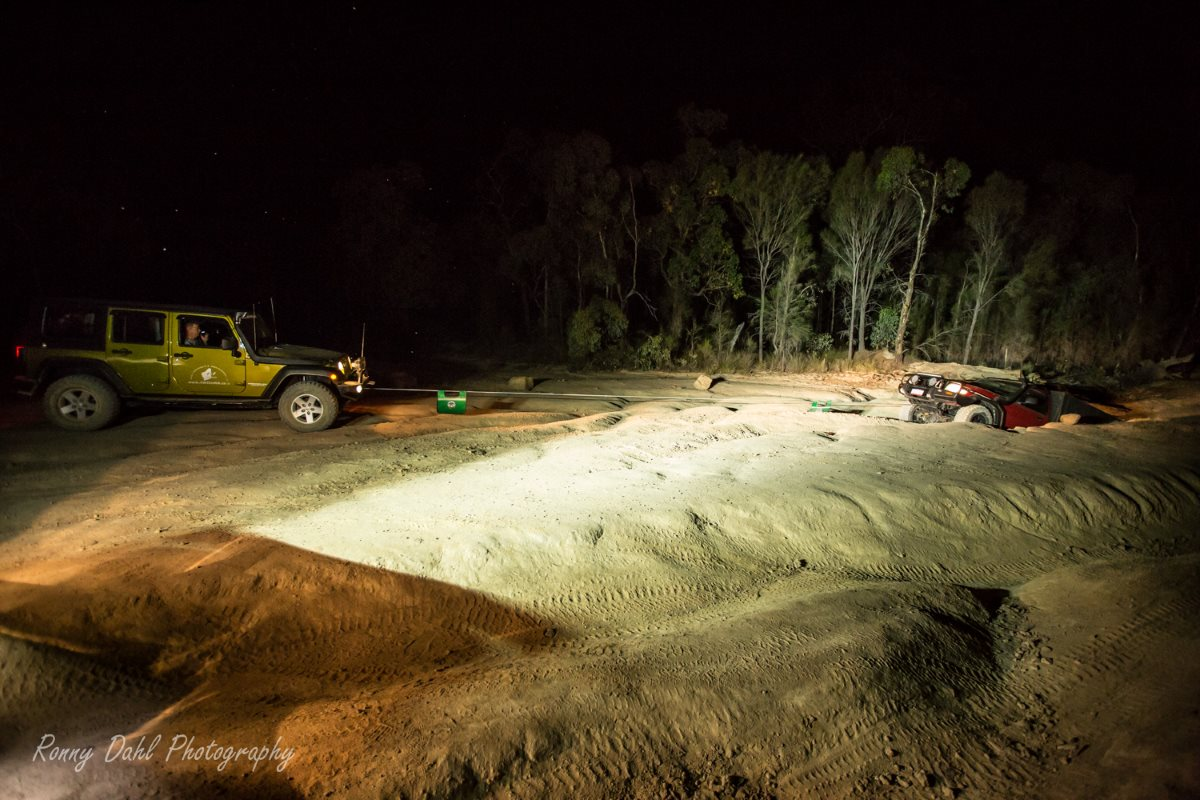 Jeep Wrangler winching out a Nissan Patrol in the dark.