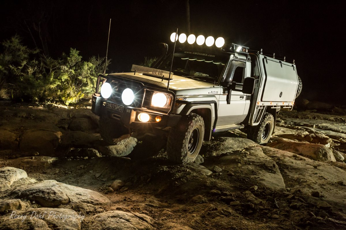 79 series Toyota LandCruiser rock climbing in the dark at Mundaring Power line, Western Australia.