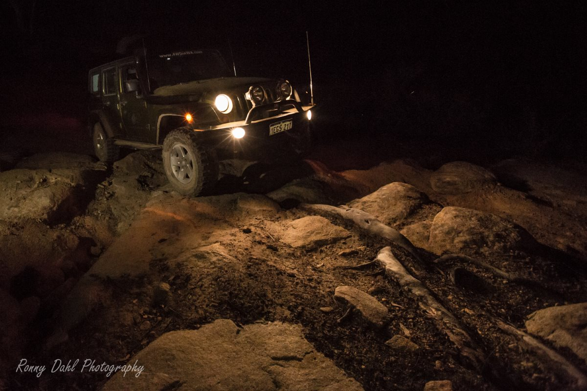 Jeep Wrangler JKU rock crawling at night.