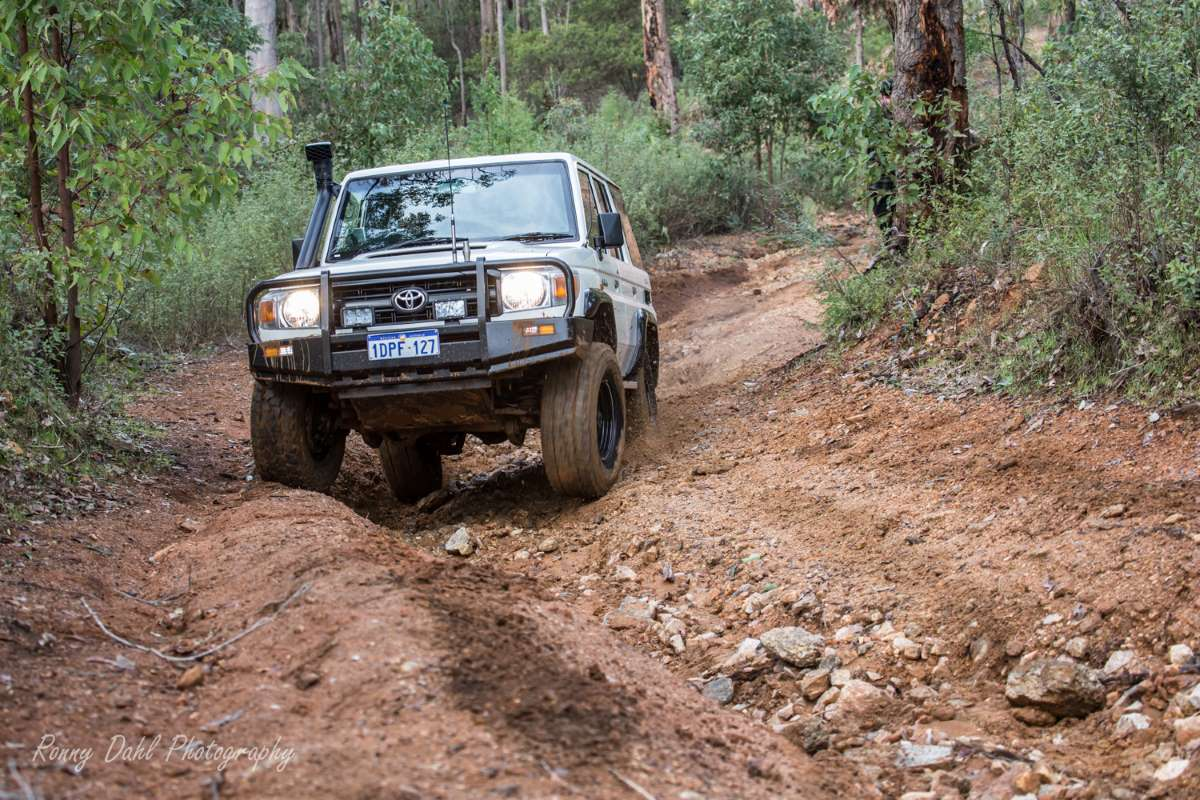 76 series Cruiser climbing a rutted hill.