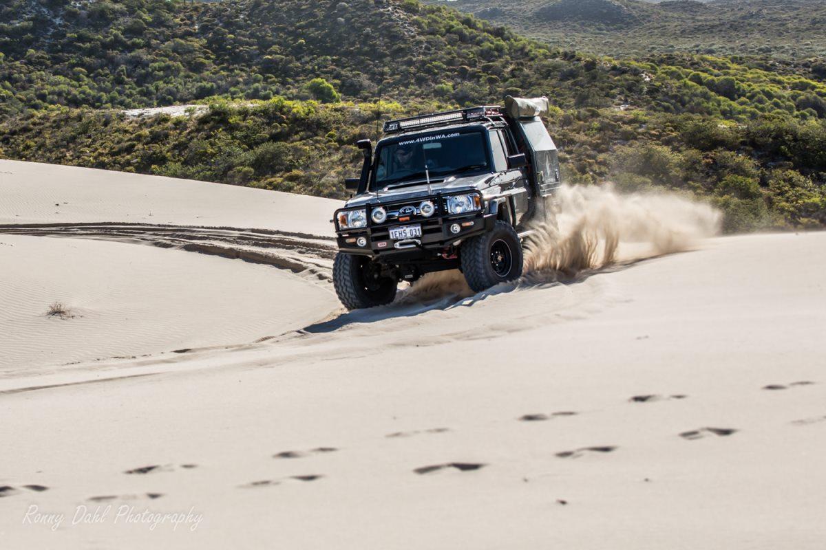 79 Series Toyota Land Cruiser cruising through sand.