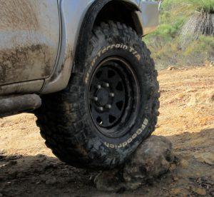 BF Goodrich Mud Terrain tire deforming around rock.