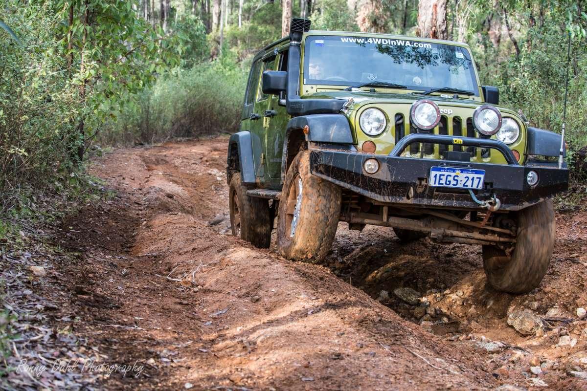 Jeep Wrangler JKU climbing a rutted hill.