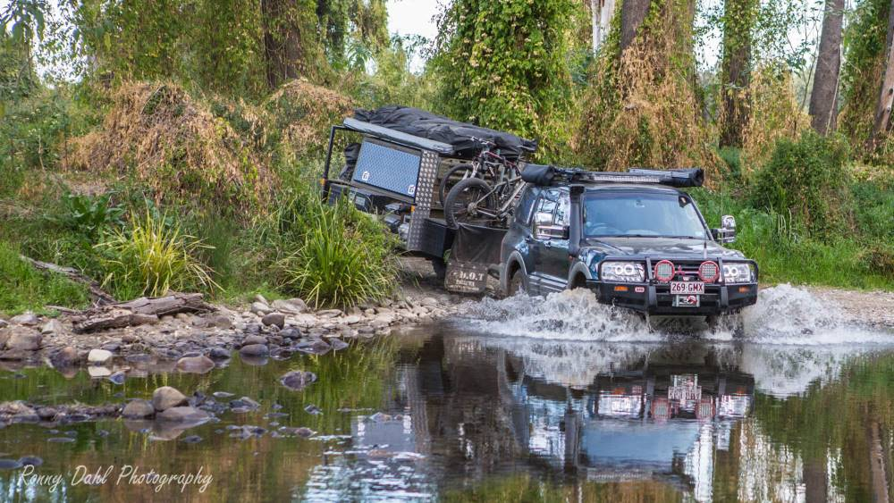 Mitsubishi Pajero with a trailer crossing a river.