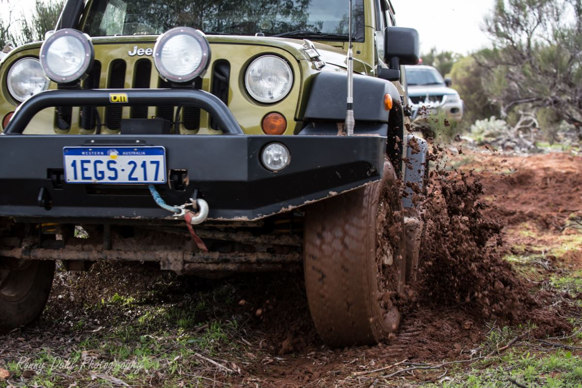 Jeep Wrangler moving through mud.