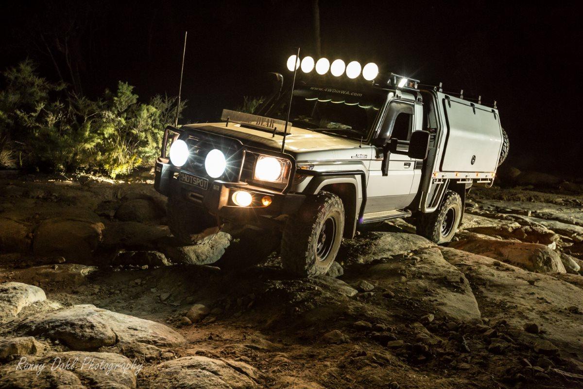 79 series Toyota LandCruiser rock climbing in the dark at Mundaring Power line, Western Australia.
