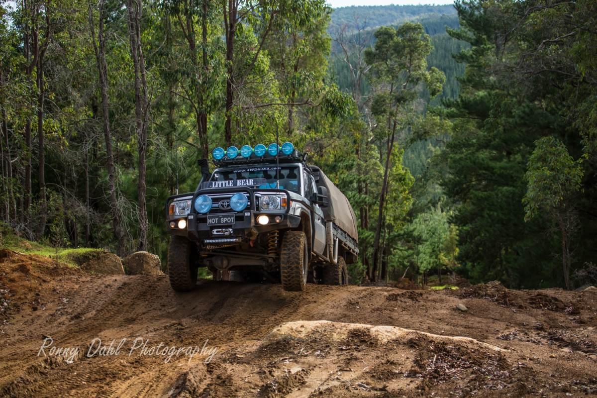 Toyota Land Cruiser climbing muddy hill in Brunswick. Western Australia.